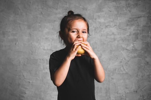 Портрет маленькой девочки счастья есть зеленое яблоко на сером фоне.