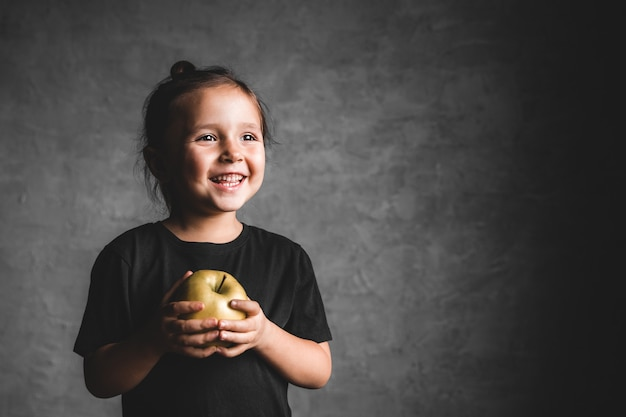 Портрет маленькой девочки счастья есть зеленое яблоко на сером фоне. Premium Фотографии