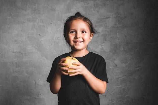 Портрет счастливой маленькой девочки, едящей зеленое яблоко на серой стене