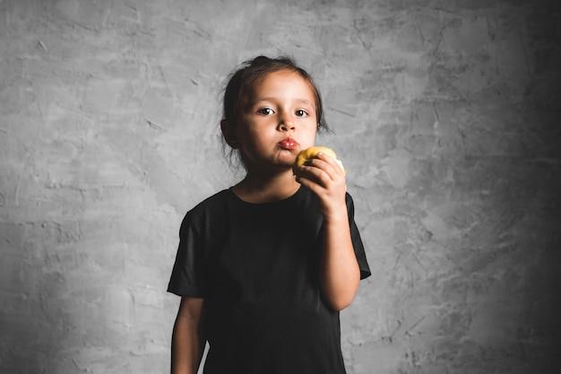 Портрет счастливая маленькая девочка ест зеленое яблоко на сером
