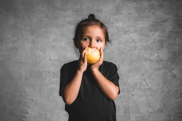 Портрет счастливая маленькая девочка ест яблоко