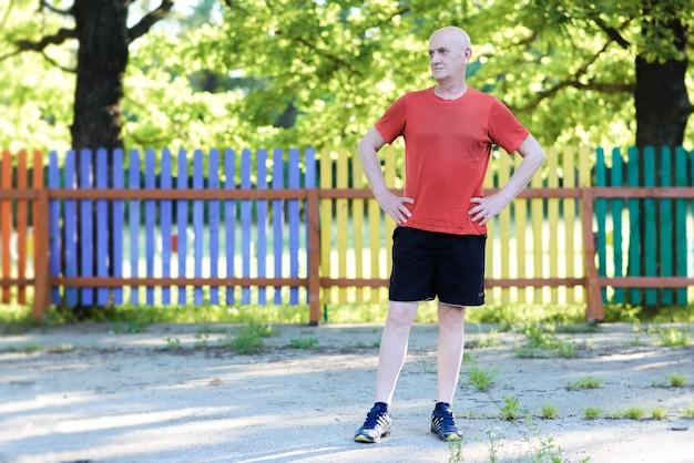 야외에서 운동 후 포즈를 취하는 행복 활성 수석 남자의 초상화