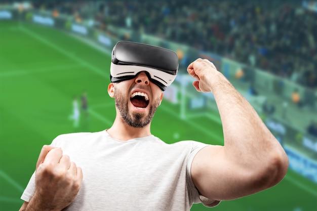 가상 현실 안경을 쓴 행복한 성인 남자의 초상화가 입을 살짝 벌리고 손을 들어 올립니다. 배경의 축구장이 흐릿합니다. 가상 현실의 개념입니다.