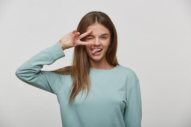 Портрет счастливой, приветливой, дружелюбной, веселой молодой женщины с каштановыми волосами, показывающей жест мира и высунувшей язык