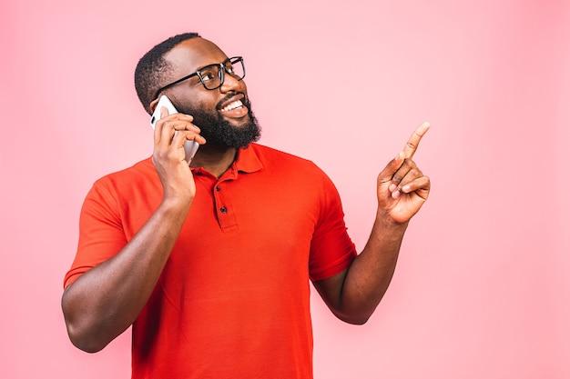 Портрет счастливого афро-американского парня разговаривает по мобильному телефону, указывая пальцем
