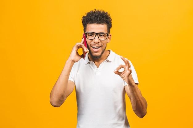 Портрет счастливого афро-американского парня разговаривает по мобильному телефону