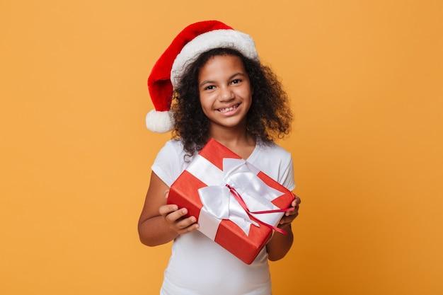 クリスマスの帽子に身を包んだ幸せなアフリカの女の子の肖像画