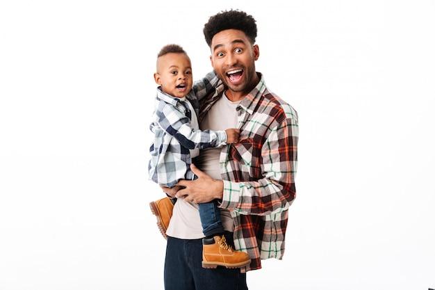 彼の幼い息子を保持している幸せなアフリカ人の肖像画