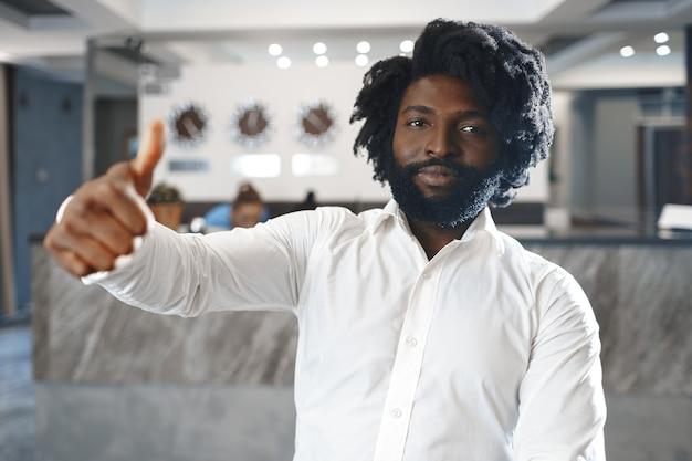 幸せなアフリカ人ホテルのマネージャーまたはホテルに立っているゲストの肖像画
