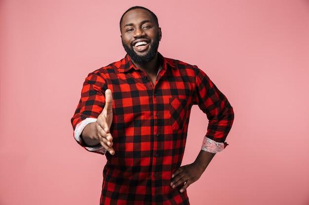Портрет счастливого африканца в клетчатой рубашке, стоящего изолированно над розовой стеной, с протянутой рукой для приветствия
