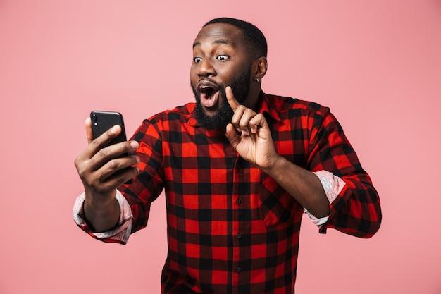 Портрет счастливого африканца в рубашке, стоящего изолированно над розовой стеной и делающего селфи