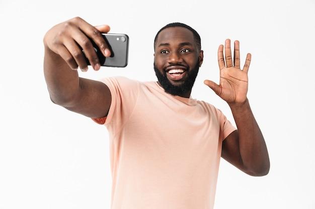 Портрет счастливого африканца в футболке, стоящего изолированно над белой стеной и делающего селфи