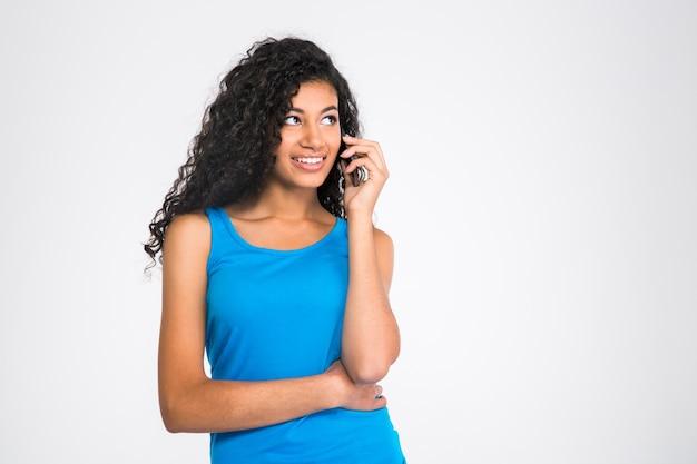 Портрет счастливой африканской женщины разговаривает по телефону и смотрит в сторону, изолированную на белой стене