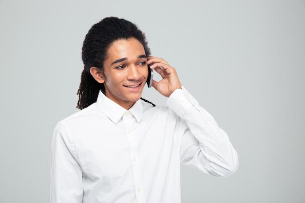 灰色の壁を越えて電話で話している幸せなアフリカ系アメリカ人実業家の肖像画