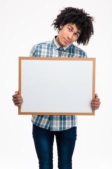 Портрет счастливого афроамериканца, держащего пустую доску, изолированную на белой стене