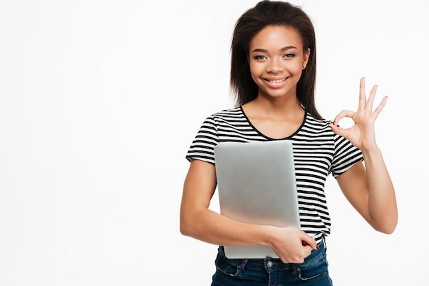 ラップトップを保持している幸せなアフロアメリカンの10代女性の肖像画