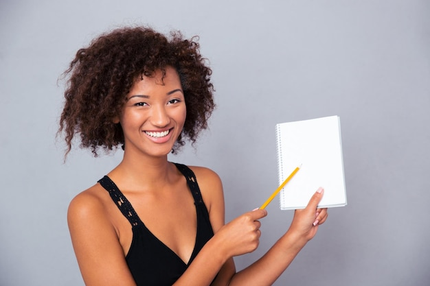 Портрет счастливой афро-американской женщины, показывающей пустой блокнот с карандашом над серой стеной