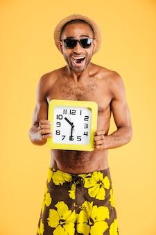 Портрет счастливого афро-мужчины в купальниках, держащего настенные часы на оранжевой стене