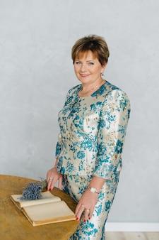 Портрет счастливой постаретой красивой женщины с цветком и книгой лаванды остается в винтажном домашнем интерьере