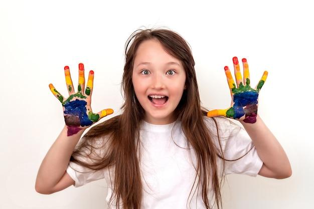 Портрет счастливой и улыбающейся девушки с разноцветными ладонями. девушка выглядит удивленной и восторженной, ее глаза широко открыты.