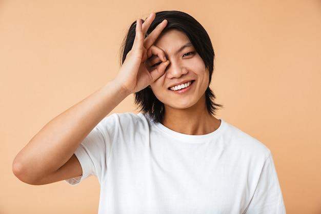 Портрет счастливого азиатского мужчины в футболке, стоящего изолированно над бежевой стеной, показывая хорошо