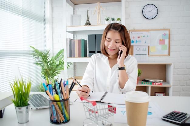 Портрет счастливой азиатской женщины после получения подтверждения заказа от клиента с помощью смартфона.