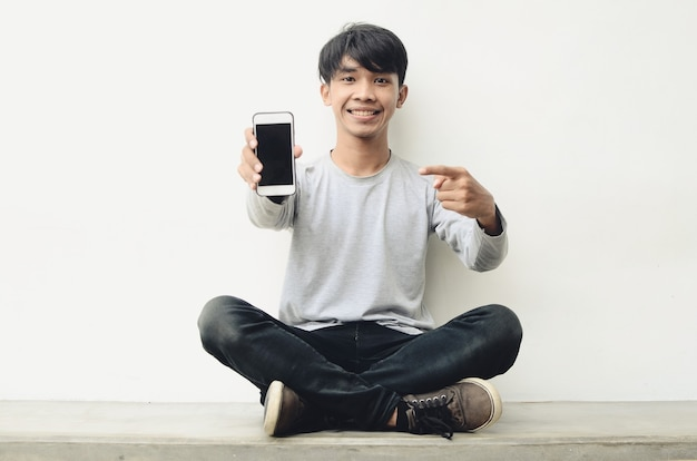 휴대 전화를 가리키는 행복 한 아시아 청소년의 초상화
