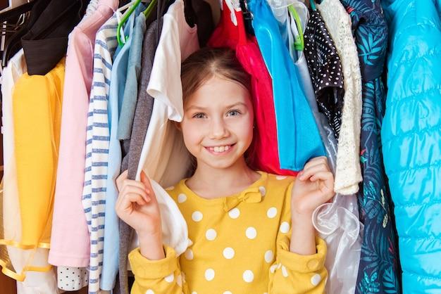 Портрет счастливой привлекательной девочки-подростка, делающей выбор в гардеробе