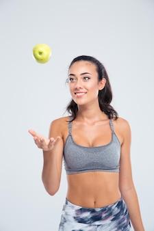 Портрет счастливой привлекательной женщины с яблоком, изолированным на белой стене