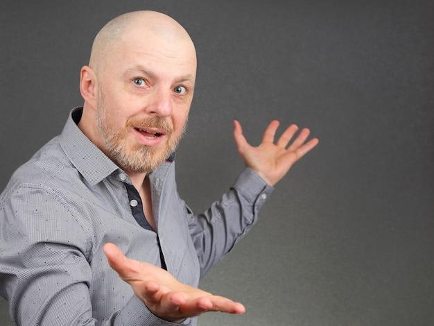 Портрет счастливого бородатого мужчины в рубашке с поднятыми руками