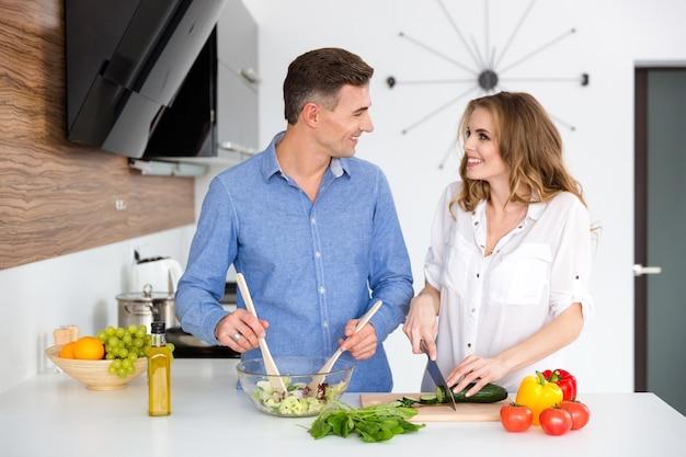 台所で一緒に料理をする幸せな美しいカップルの肖像画