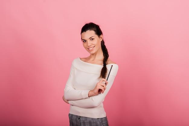 Портрет счастливой красивой улыбающейся женщины, касающейся ее лица, изолированной на синем и розовом фоне
