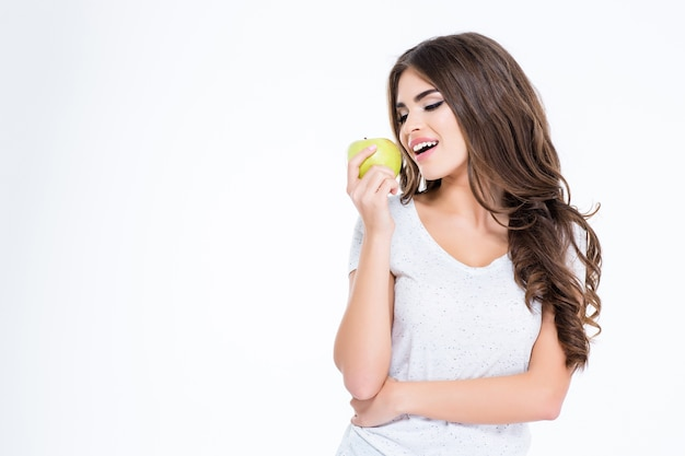 행복 한 아름 다운 여자 먹는 사과의 초상화는 흰 벽에 고립