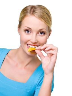 Портрет счастливой красивой женщины ест чипсы
