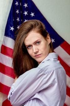 アメリカの国旗の表面に幸せな美しい若い女性の肖像画