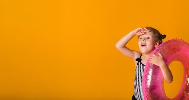 텍스트에 대 한 공간을 가진 노란색 표면에 분홍색 풍선 원을 들고 스트라이프 수영복에 행복 한 금발 소녀의 초상화