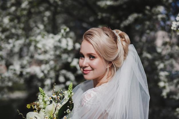 屋外で髪型と花の花束を持つ幸せな花嫁の肖像画