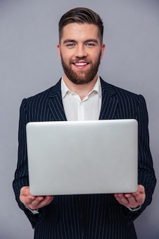 Портрет счастливого бизнесмена, держащего ноутбук над серой стеной и смотрящего в камеру на сером фоне