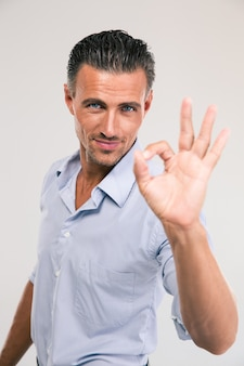 Портрет счастливого бизнесмена, показывающего знак ок с пальцами над серым пространством