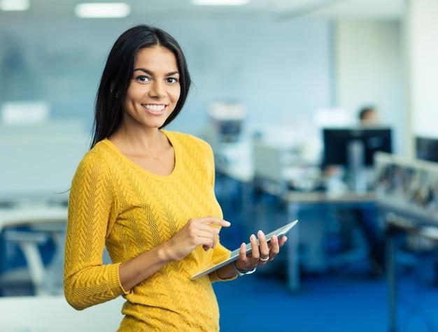 Портрет счастливой бизнес-леди в свитере, стоящей с планшетным компьютером в офисе