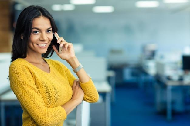 Портрет счастливой деловой женщины разговаривает по телефону в офисе