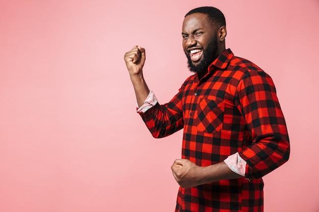 Портрет счастливого случайного африканца, стоящего изолированно, празднуя успех