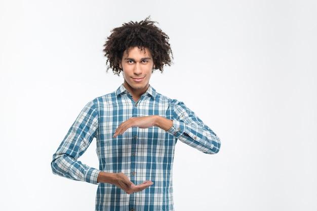 흰 벽에 고립 된 보이지 않는 뭔가를 들고 행복 캐주얼 아프리카 계 미국인 남자의 초상화