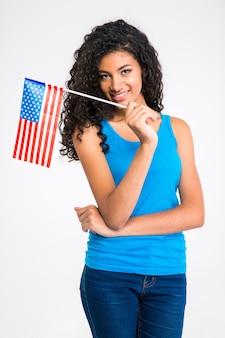 白い壁に隔離され、正面を見て米国旗を保持している幸せなカジュアルなアフリカ系アメリカ人女性の肖像画