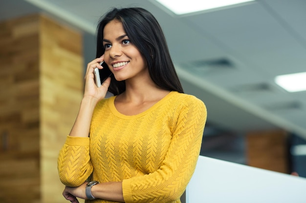 Портрет счастливой повседневной деловой женщины разговаривает по телефону в офисе и смотрит в сторону