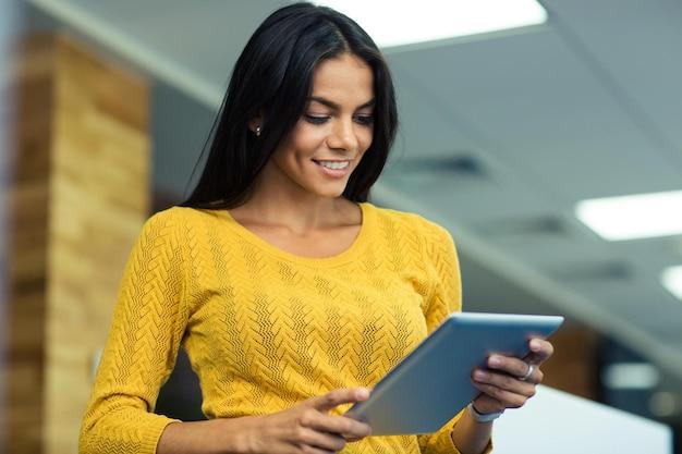 Портрет счастливой деловой женщины, использующей планшетный компьютер в офисе
