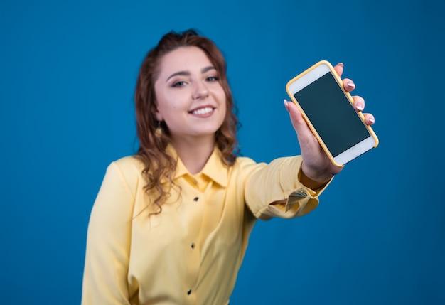 Портрет счастливой вскользь женщины показывая пустой экран смартфона изолированный на голубой предпосылке.