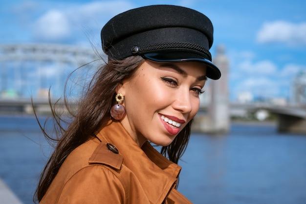 Портрет счастливой кавказской женщины на набережной реки в черной кепке и коричневой куртке в солнечный день