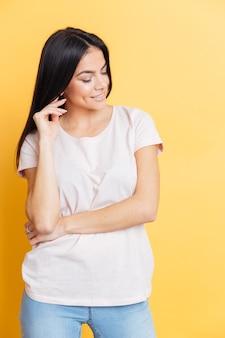 黄色の壁の上に立っている幸せな魅力的な女性の肖像画
