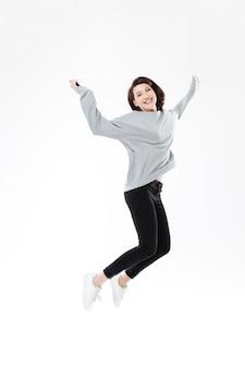 Портрет счастливой жизнерадостной женщины скача и празднуя успех